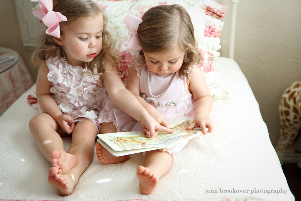 sisters reading during one year photo session celebrating baby girl's birthday