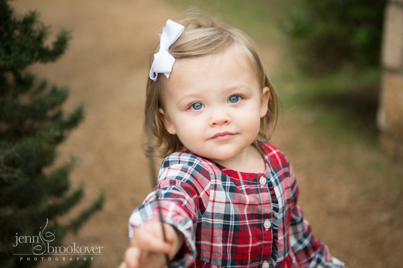 baby girl with blue eyes outside in red plaid outfit