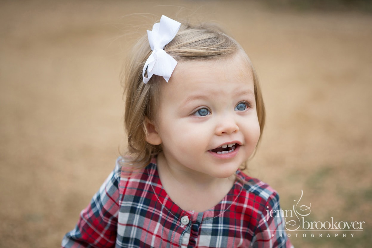 close up of two year old in plaid top and white bow taken at Tejas Rodeo