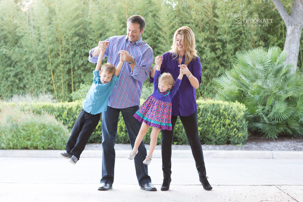 family laughing and swinging their children dressed in purple and teal at Landa Library