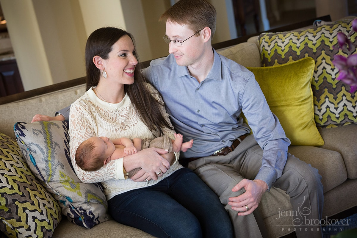 newborn at home with mom and dad on bright couch