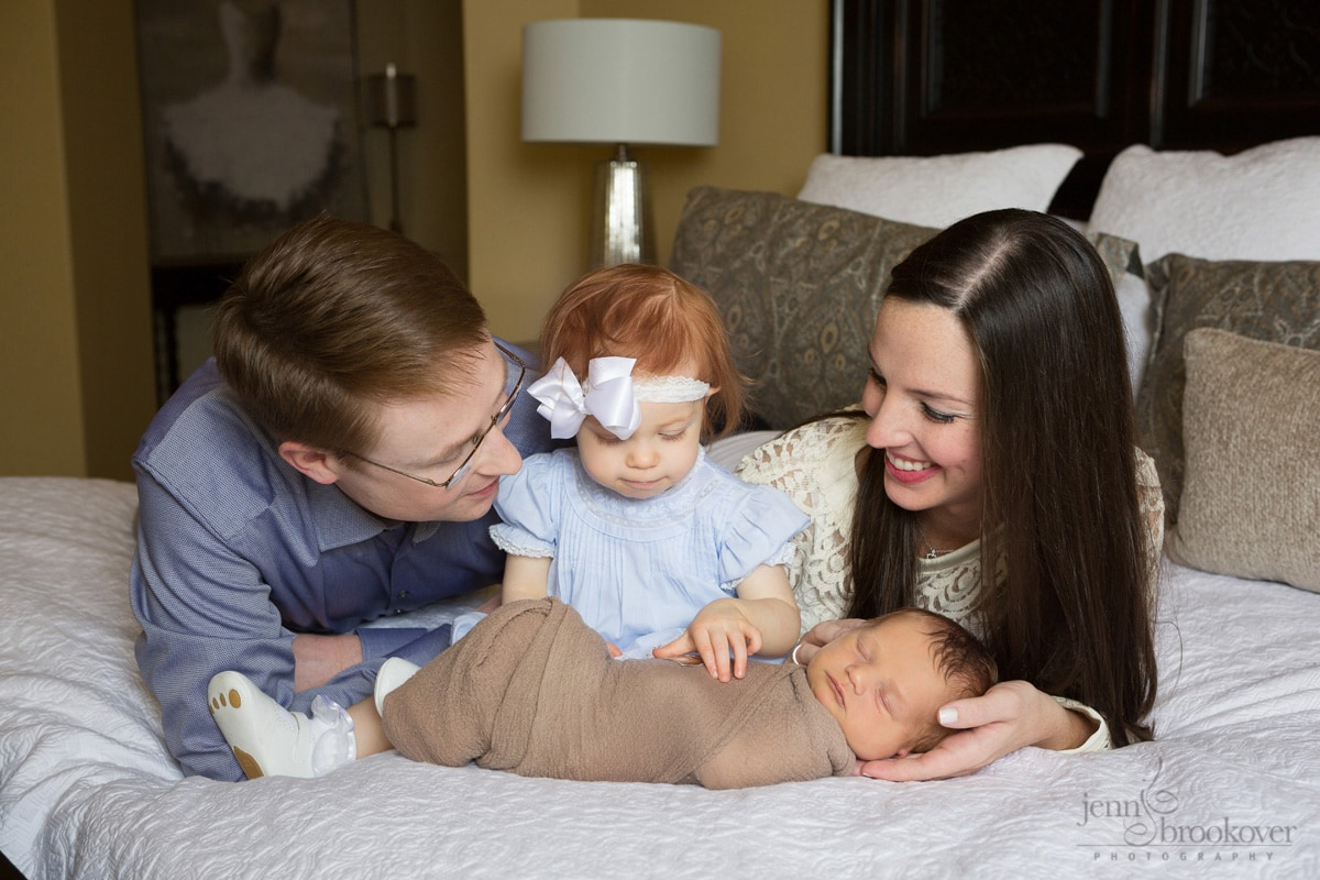 newborn family on bed admiring new baby brother