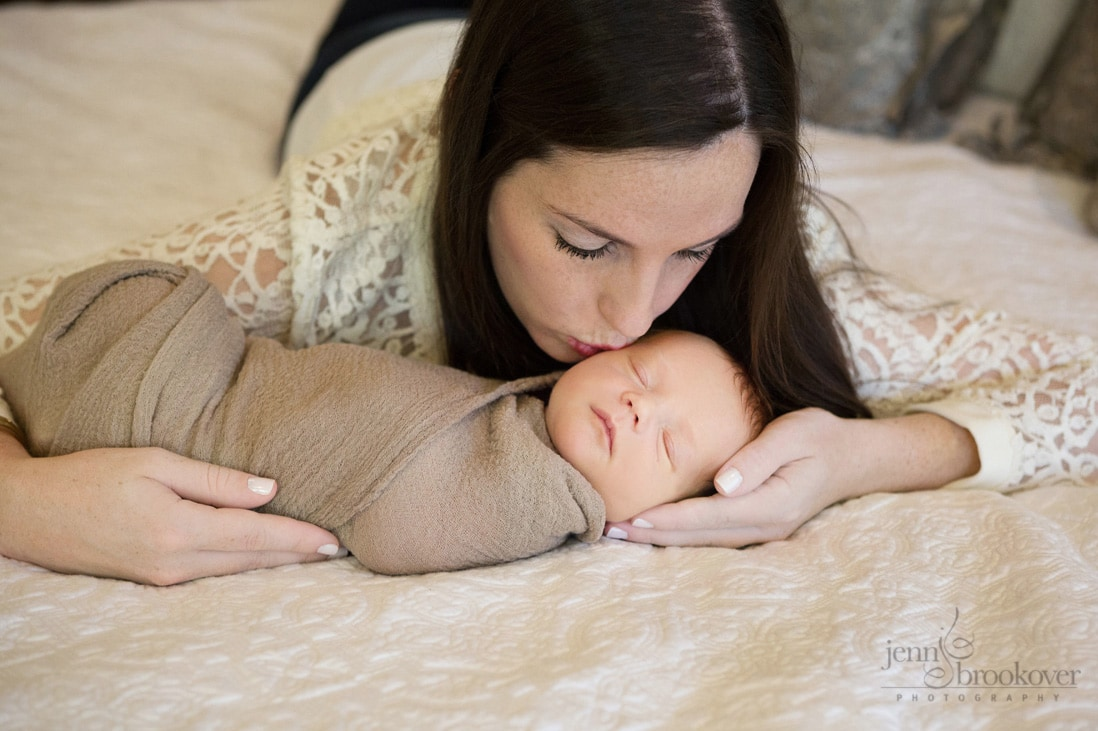 newborn being kissed by mom during photo session at home