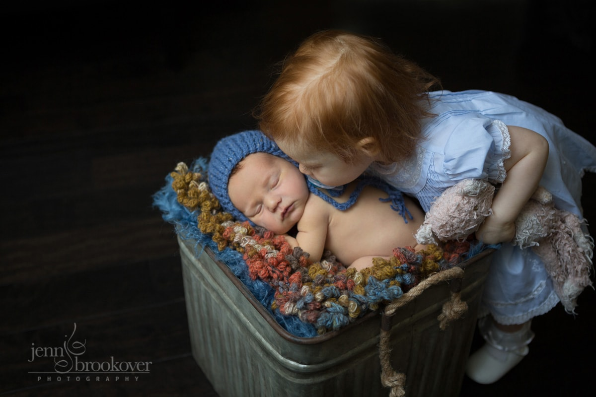 big sister kissing baby brother during newborn photo session