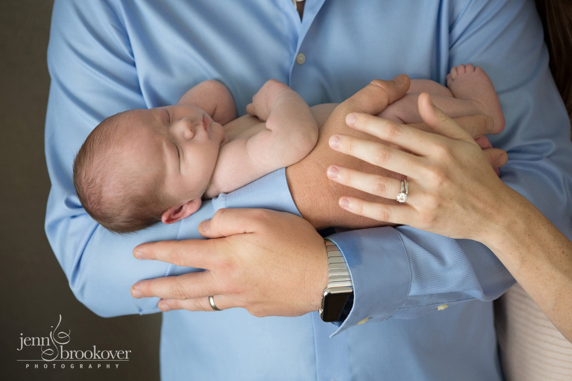 mom and dad holding newborn boy during photo session