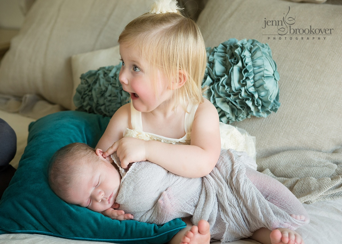 excited big sister snuggling with her baby brother