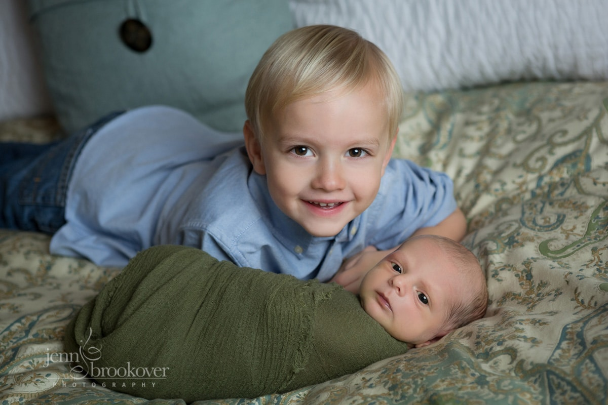 newborn with big brother smiling during photo session at home