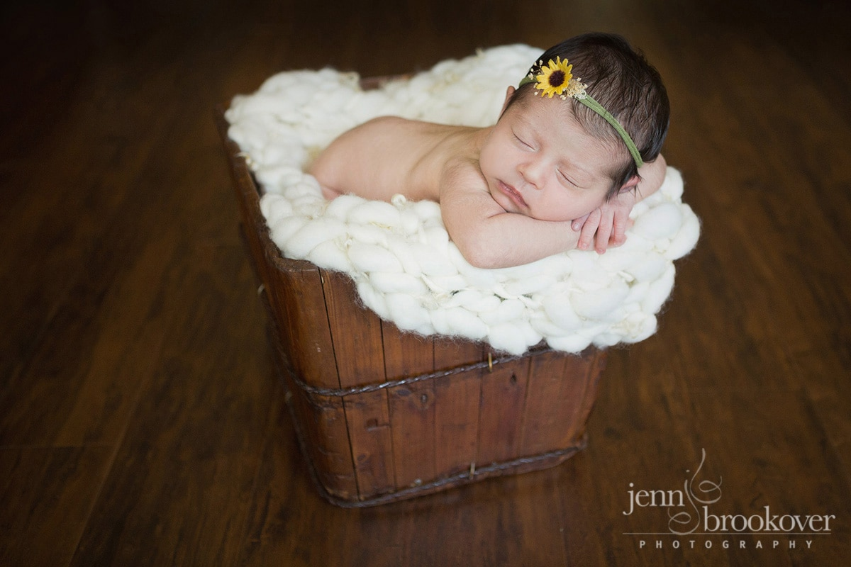 newborn in a bucket with a sunflower headband on wood floor
