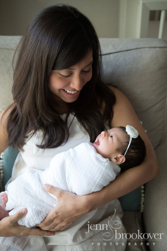 mom holding smiling newborn during lifestyle session at home in San Antonio