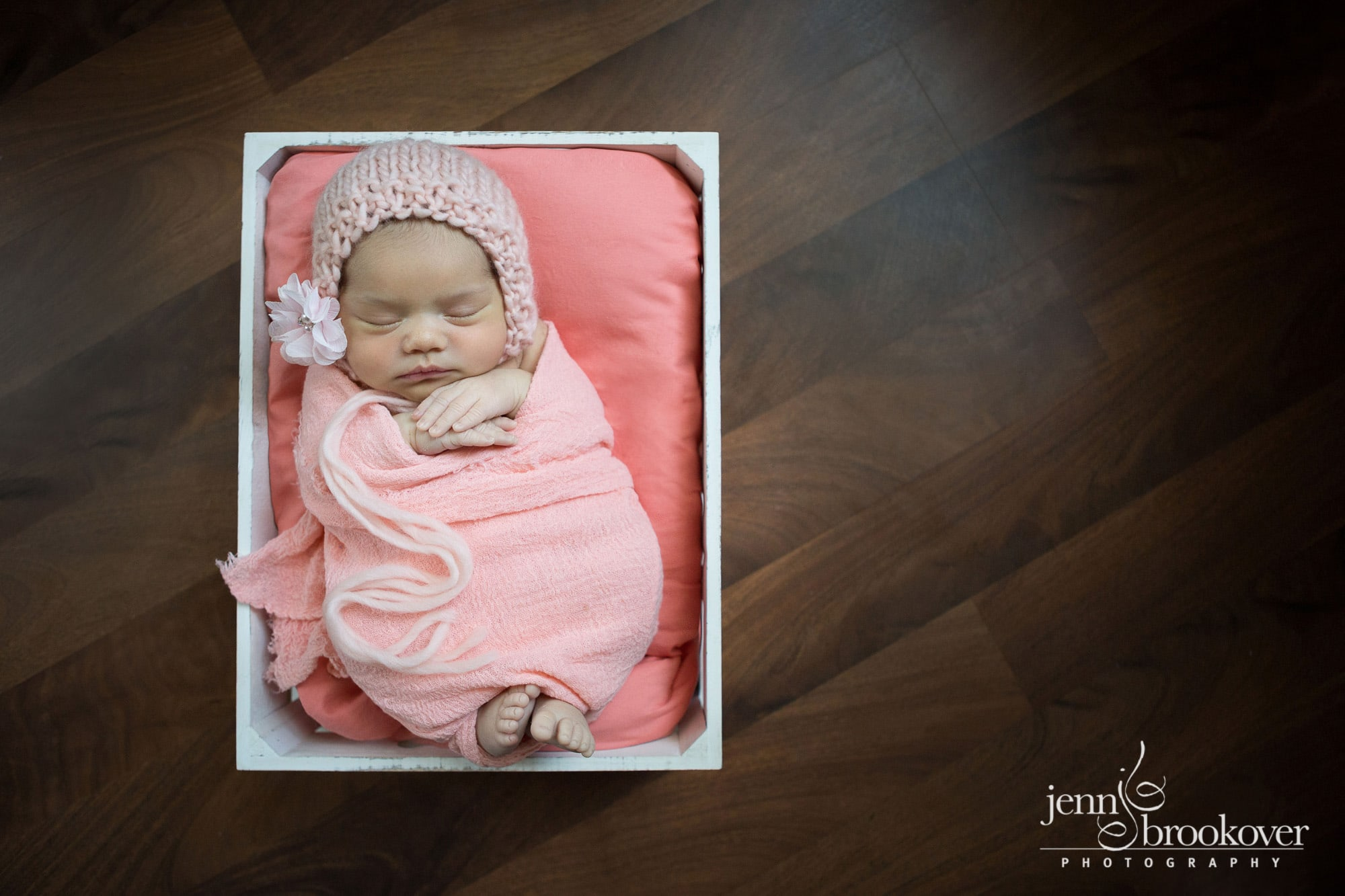newborn wrapped in peach and coral in a white basket on a wood floor by Jenn Brookover Photography in San Antonio