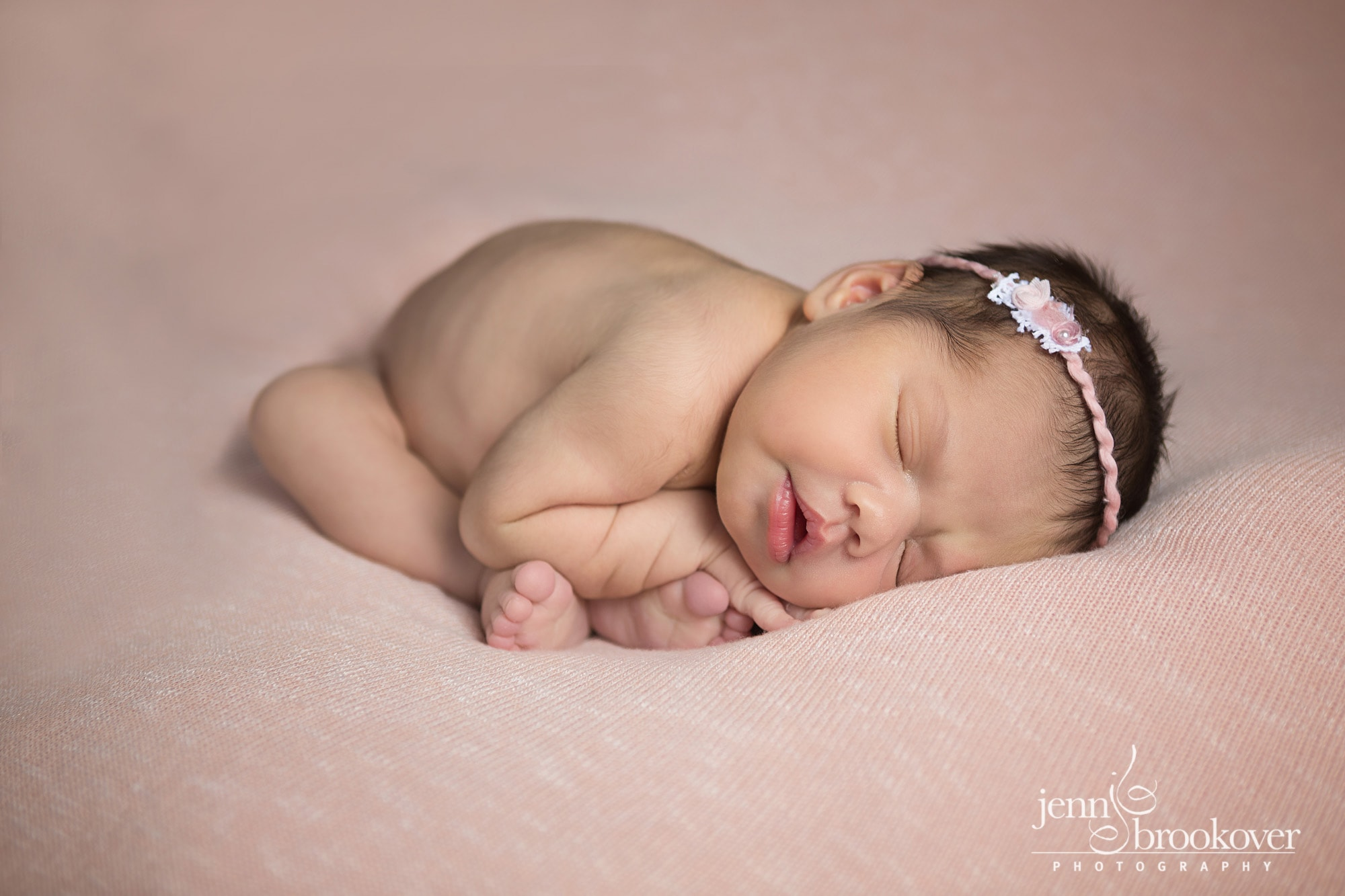 newborn curled up on peach, headband by Devoted Knits taken by Jenn Brookover in San Antonio