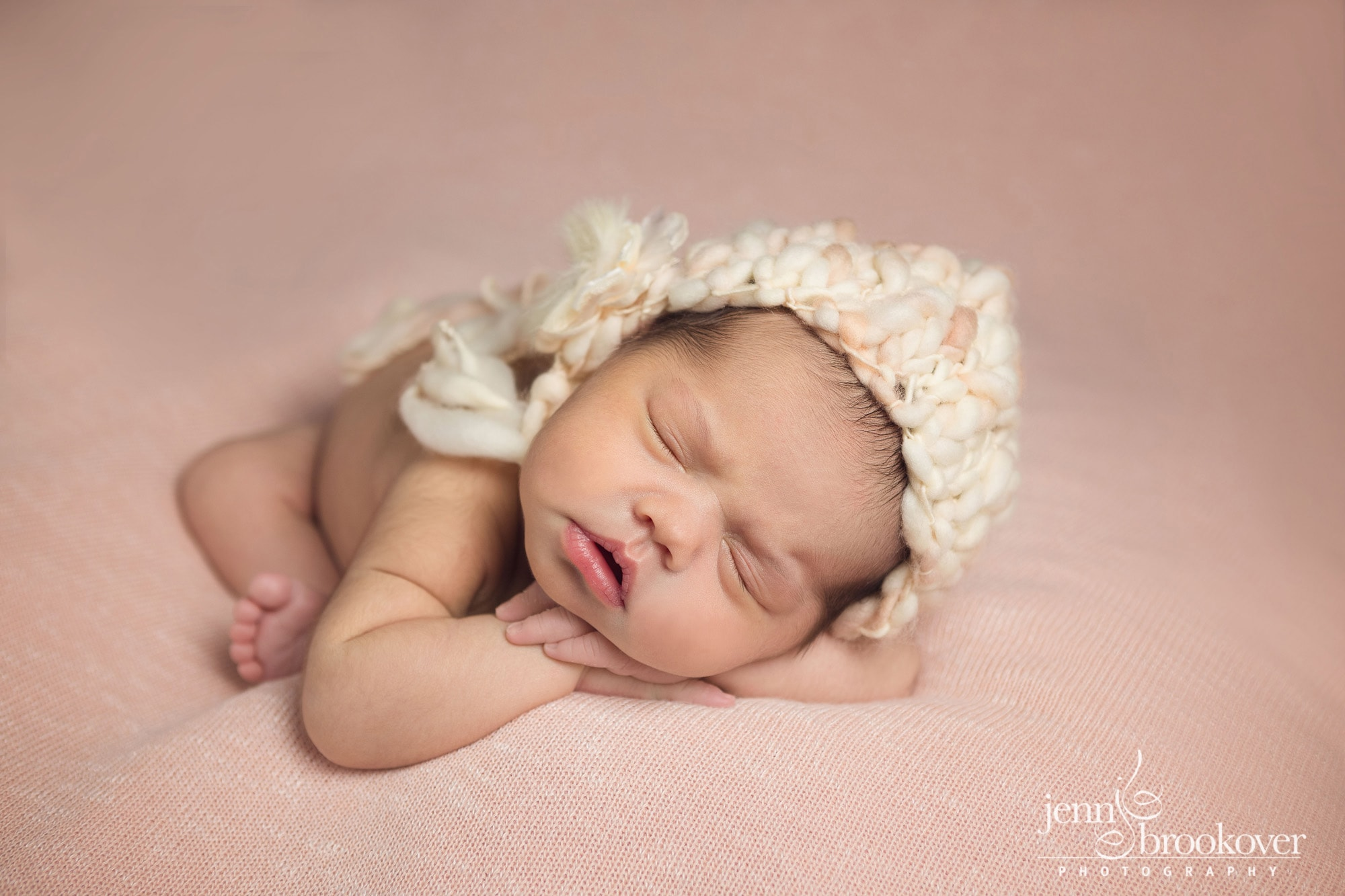 newborn portrait in peach and cream knitted hat, curled up during her session with Jenn Brookover Photography