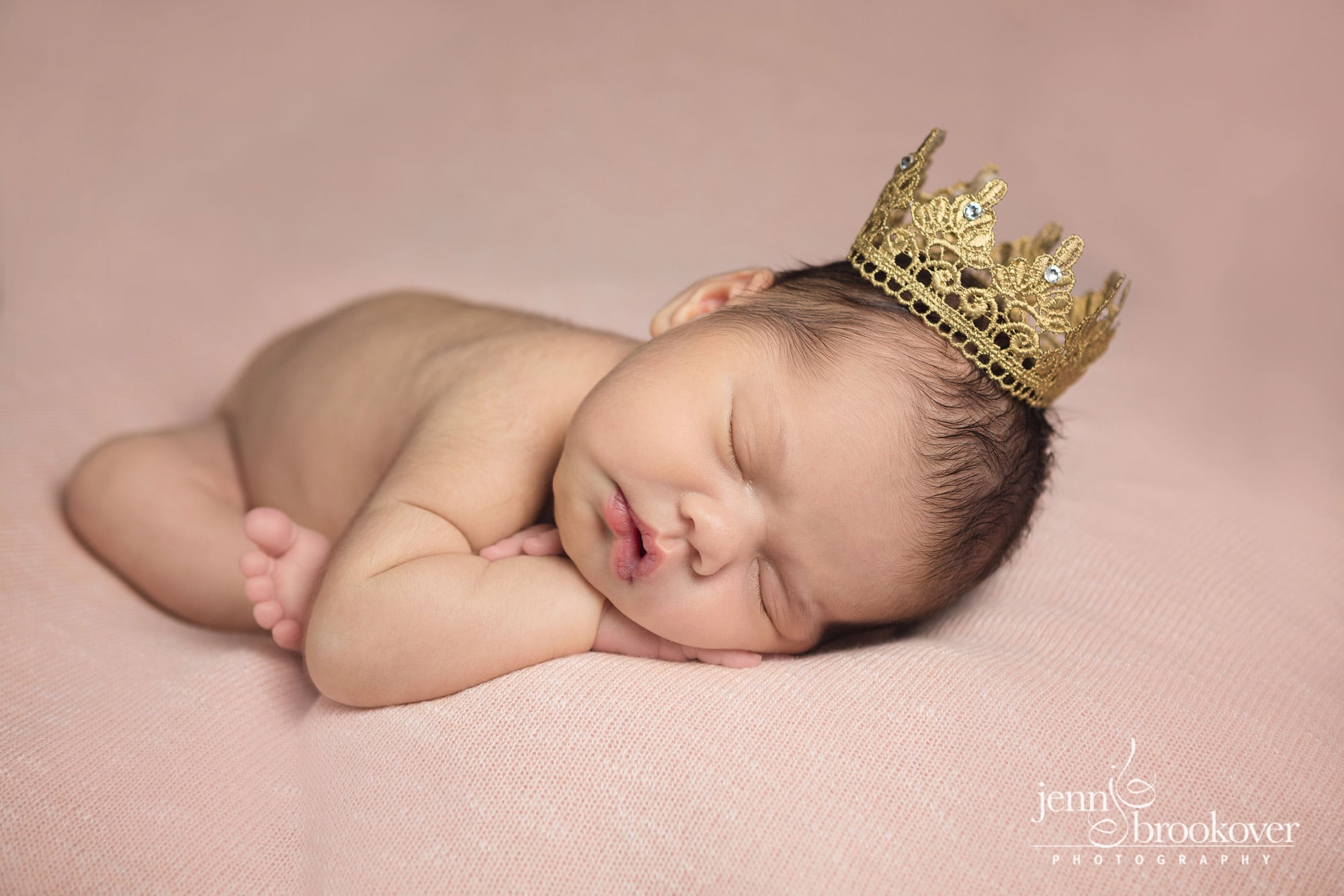 baby girl with a gold crown on with pink background taken by Jenn Brookover in San Antonio Texas