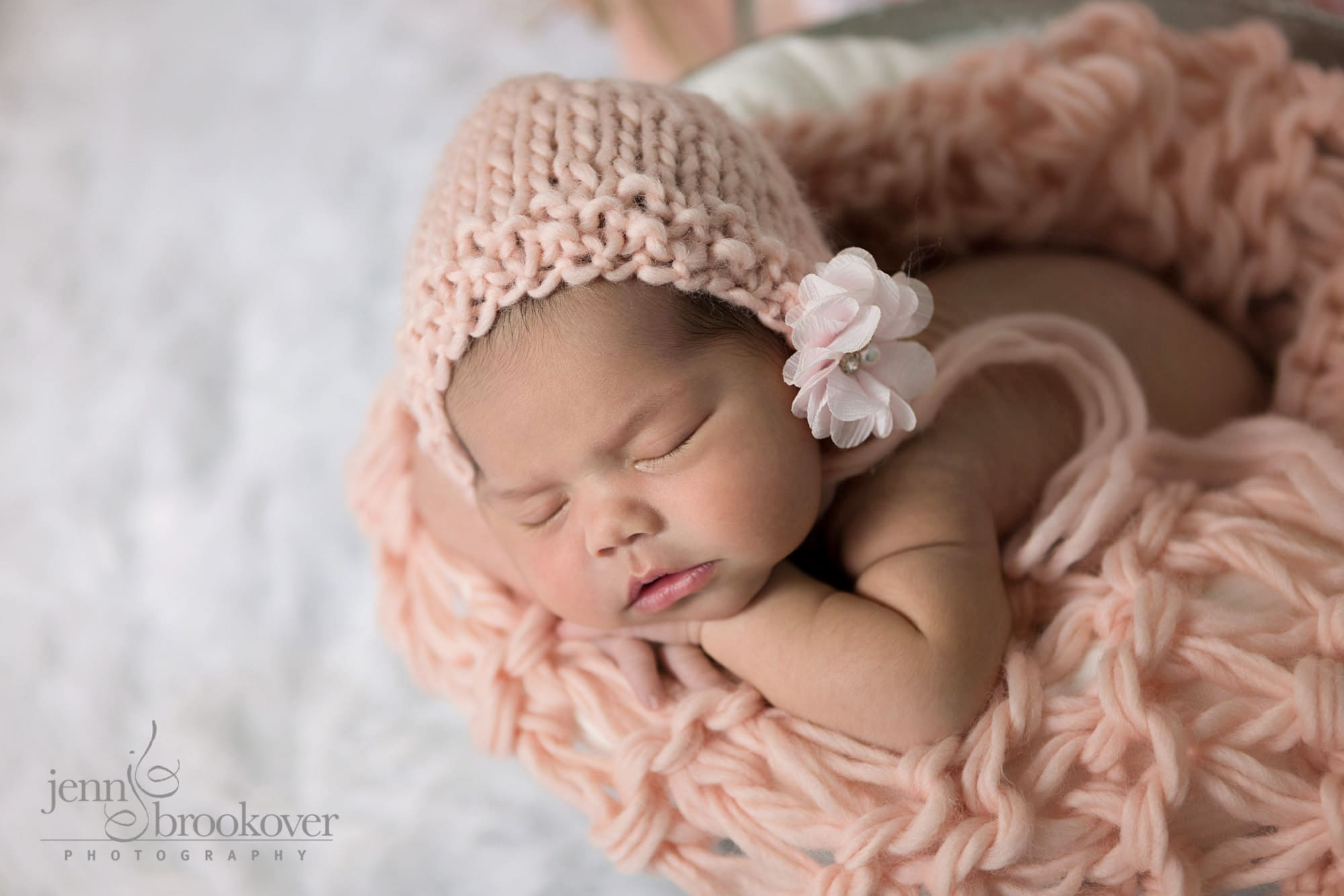 newborn in a handmade hat peach snuggled up for her newborn portrait session taken by Jenn Brookover in San Antonio, Texas