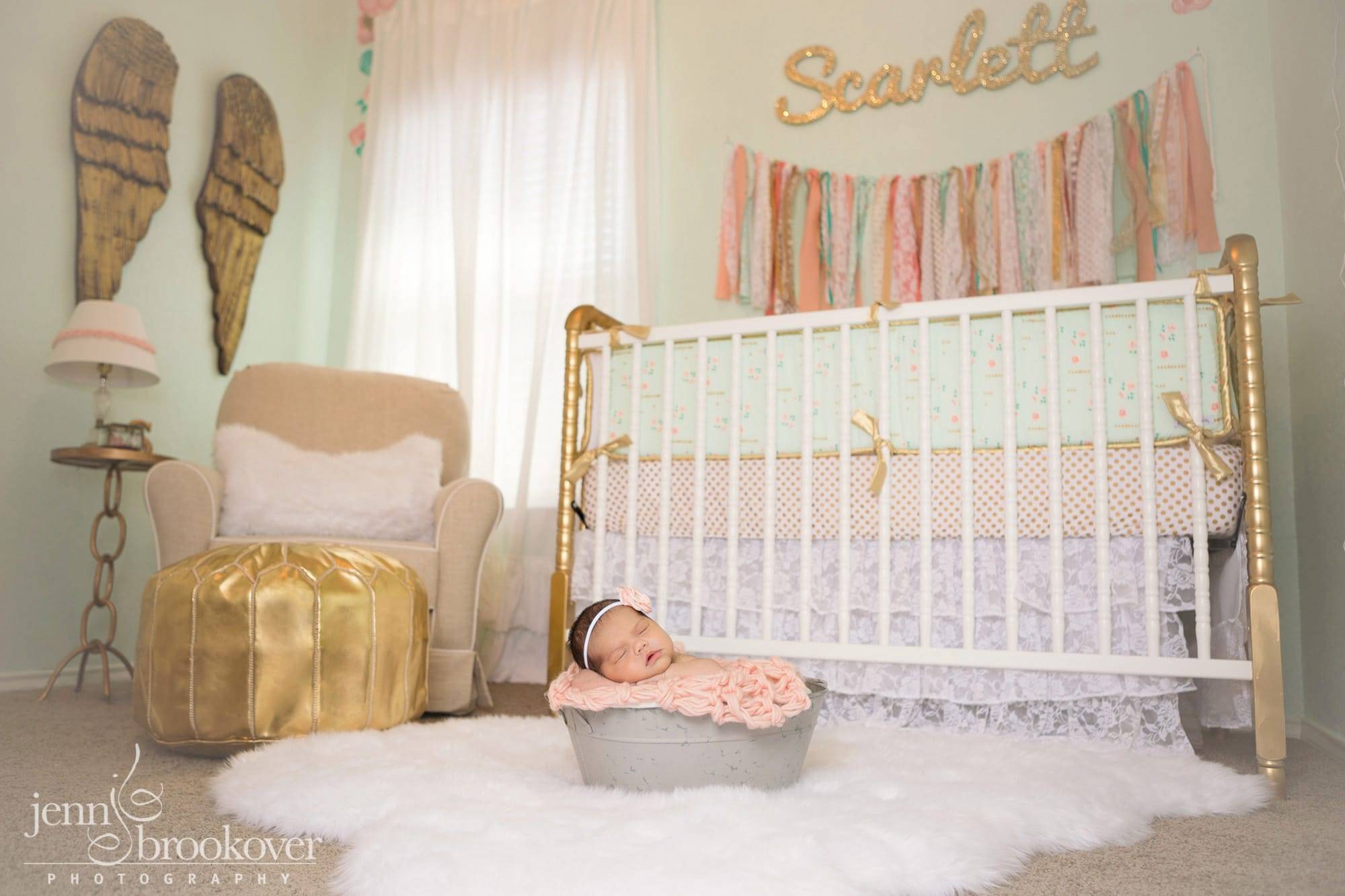gorgeous peach, mint and gold nursery designed by Nursery Couture, newborn in a bucket sleeping during her photo session with Jenn Brookover in Texas
