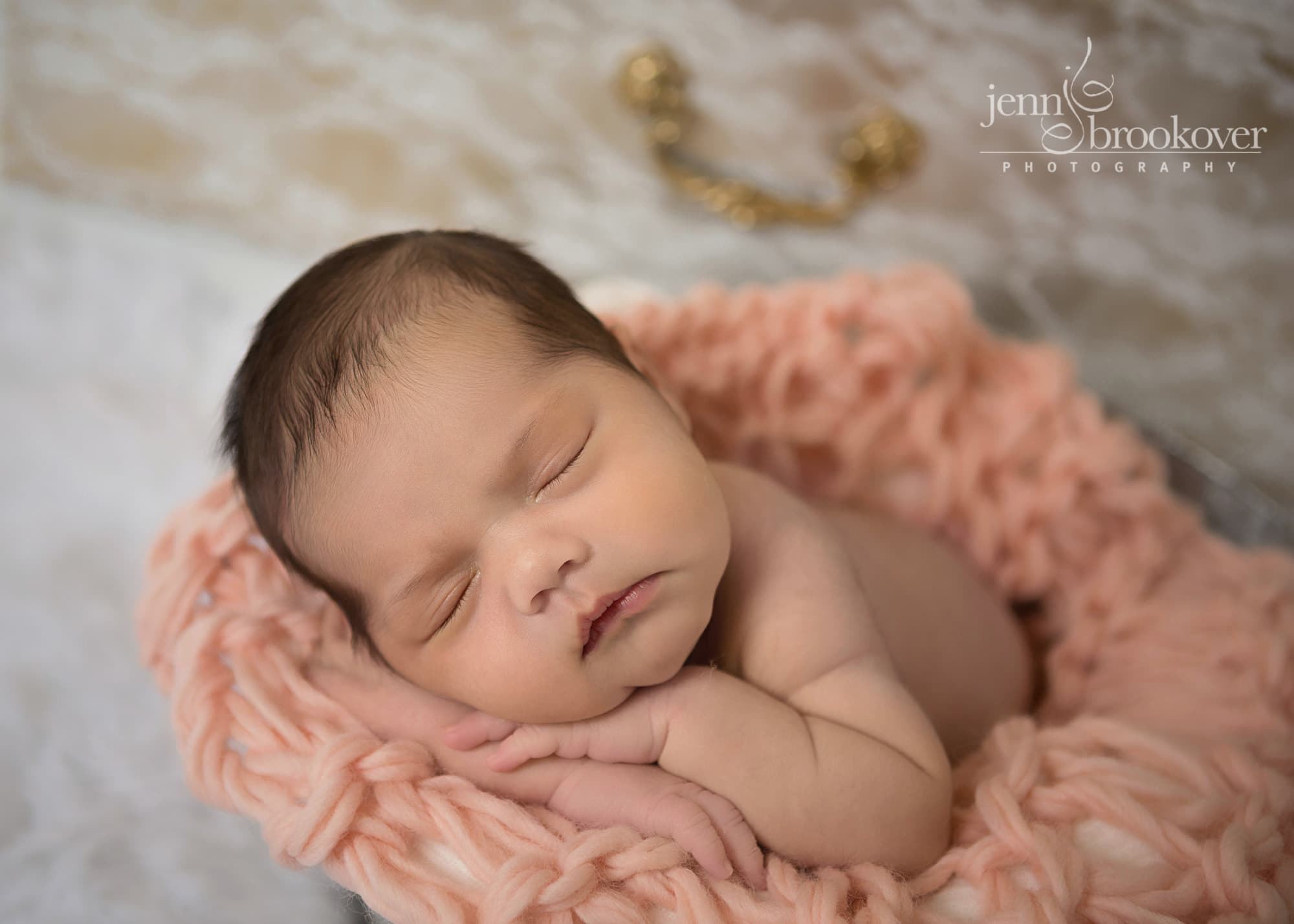 close up of a newborn baby girl in peach blanket sleeping during her photo session with Jenn Brookover in Texas