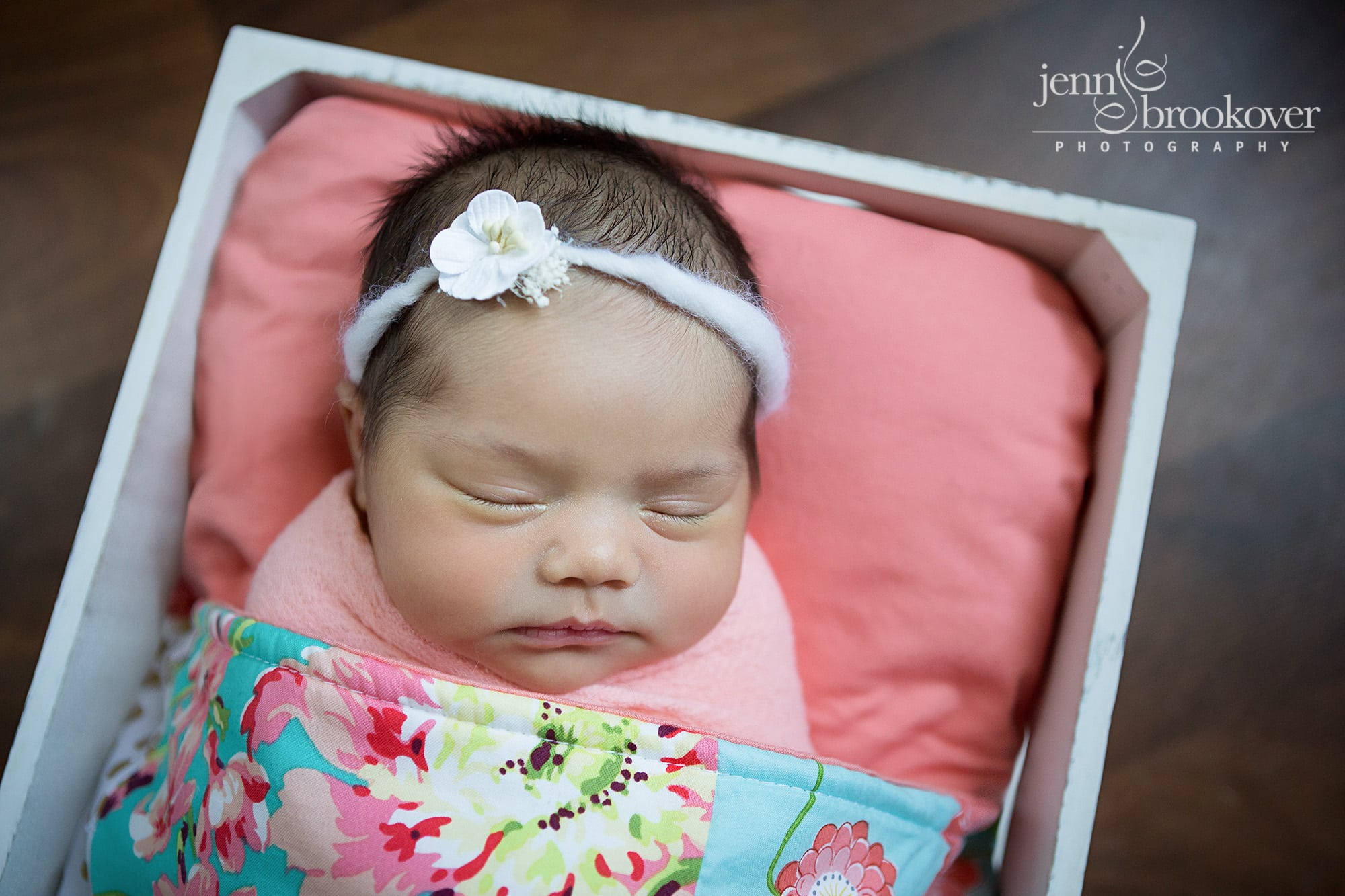 newborn baby girl in a coral, pink and teal quilt and white headband taken by Jenn Brookover in San Antonio