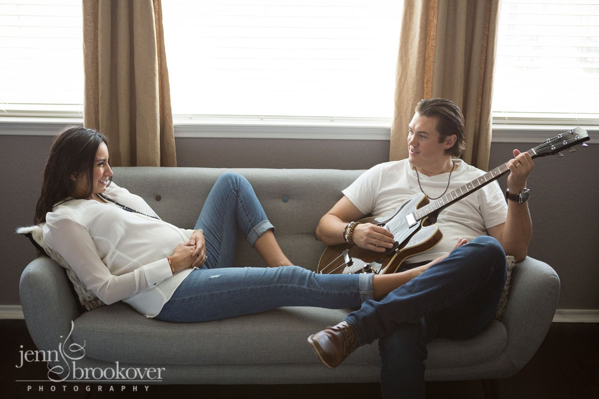 dad and mom on couch with guitar during maternity photo session at home