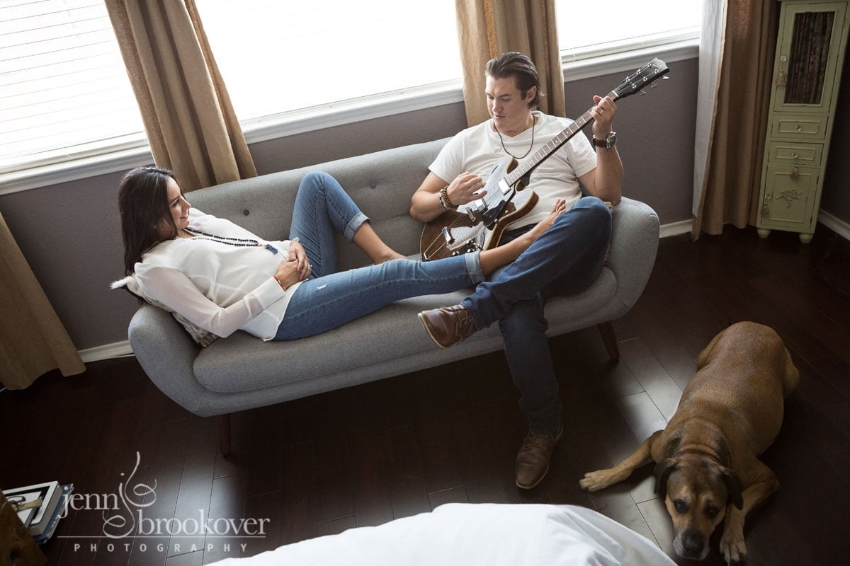 mom and dad on couch with dog during their at home maternity session