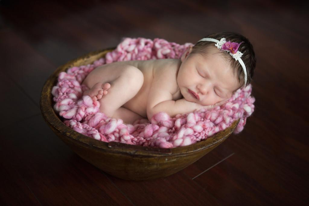 newborn on pink  blanket wearing sweet headband by Devoted Knits
