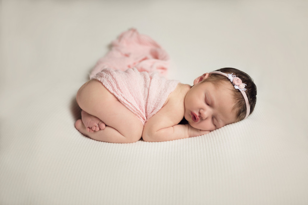 newborn on white with pink wrap and headband asleep during portrait session in San Antonio