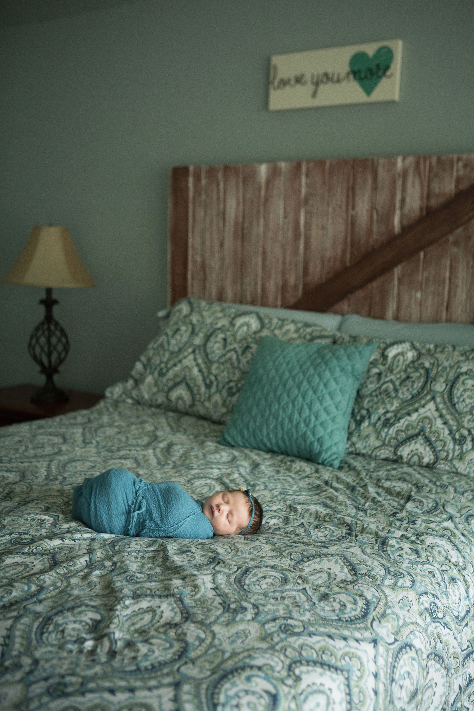 baby on bed during newborn photo session at home on Restoration Hardware bedding