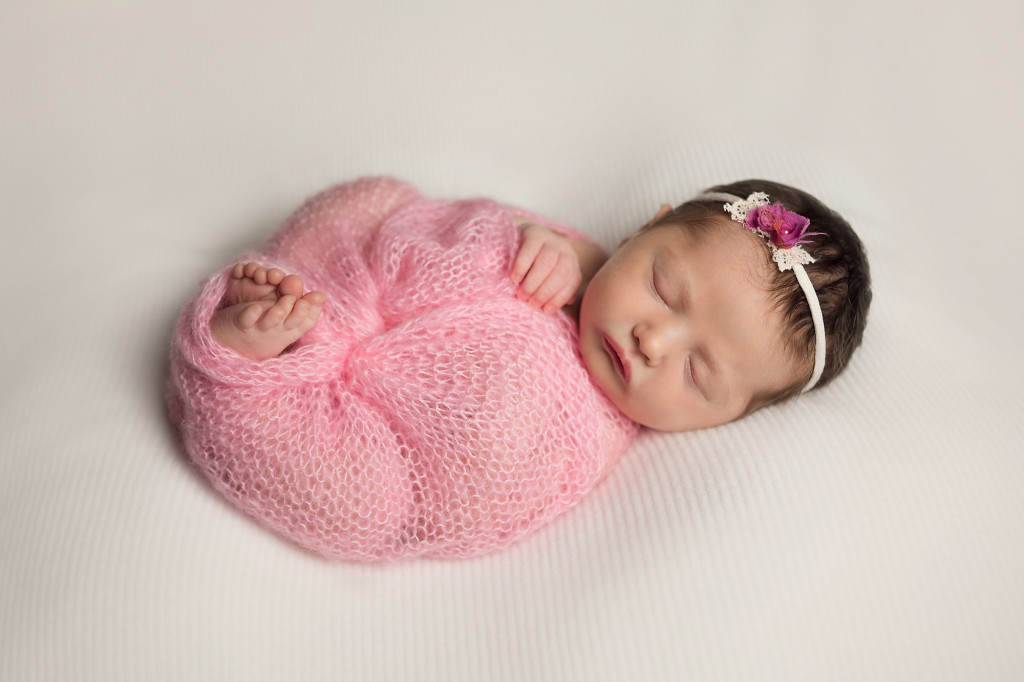 newborn wrapped up in pink on white backdrop