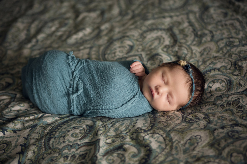newborn baby on bed at home wrapped in teal and wearing a Devoted Knits Headband