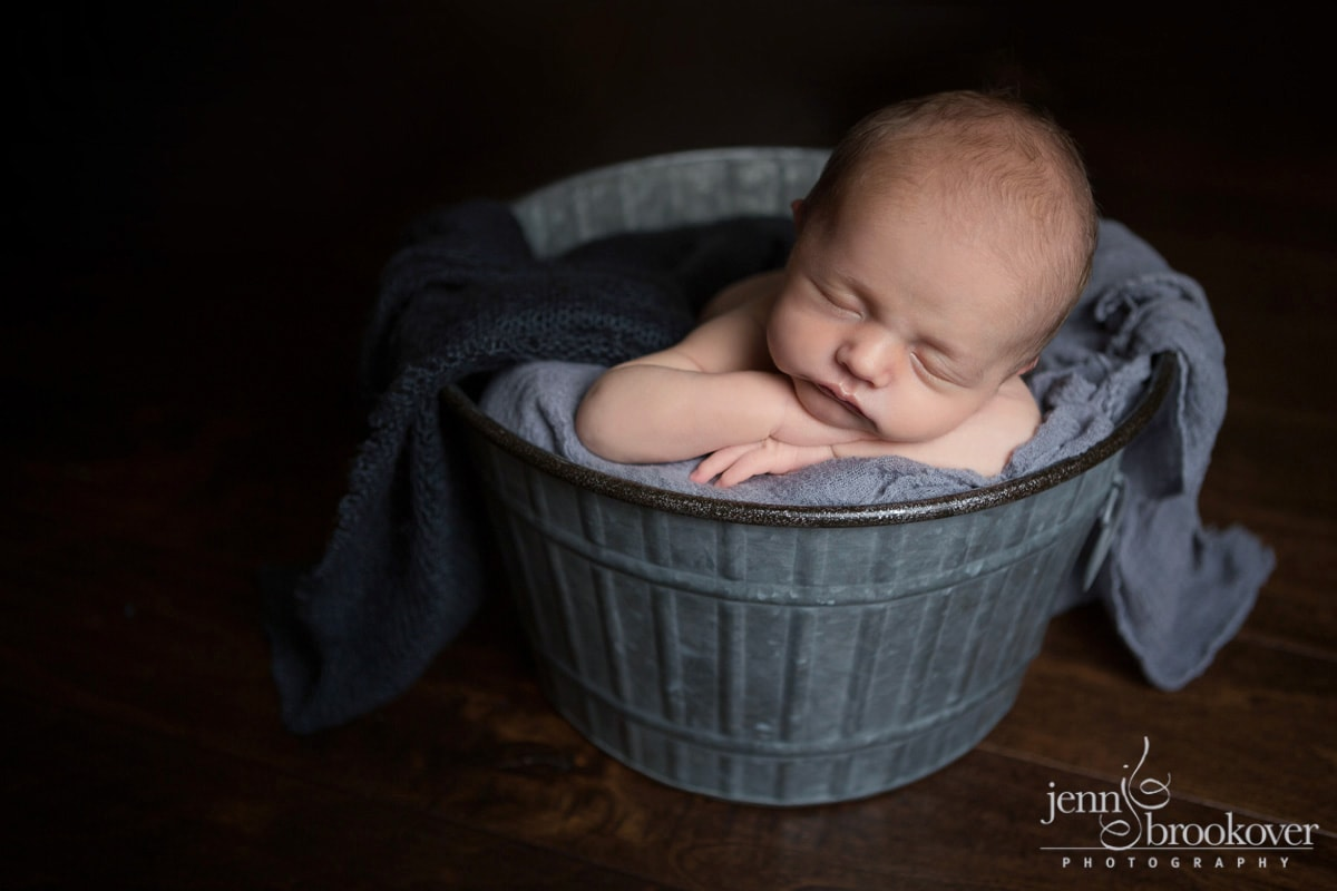 sweet baby boy newborn asleep in a bucket surrounded by gray during his newborn session at home in Alamo Heights