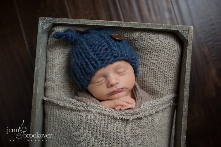 newborn boy in blue hat tucked into brown fabric bed on wood floor taken by Jenn Brookover