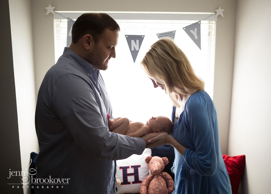 backlit image of mom, dad and baby taken during newborn photo shoot with Jenn Brookover in San Antonio