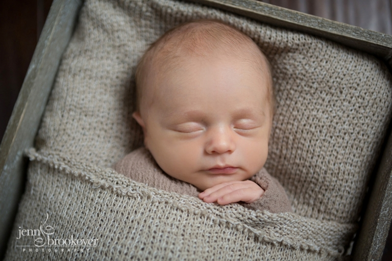 baby boy sleeping during his newborn session with sweet smile taken during newborn session in San Antonio by Jenn Brookover
