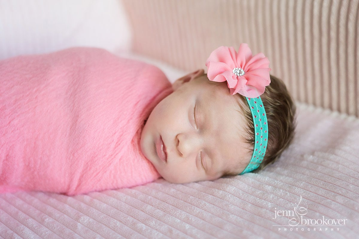 newborn photography at home in San Antonio, Texas, baby in pink with a headband