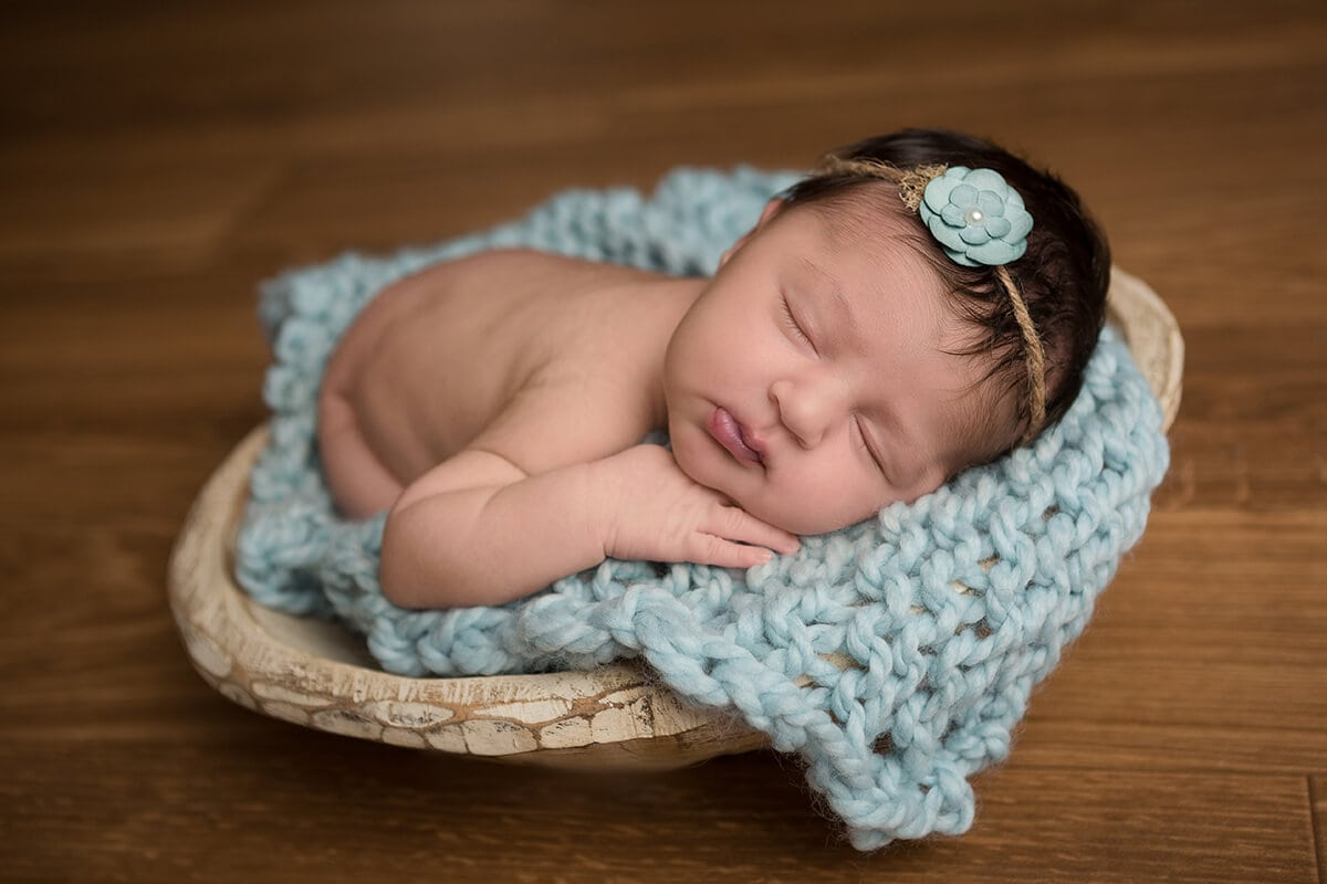 baby girl on a mist blue handmade blanket by Devoted Knits with a paper flower headband