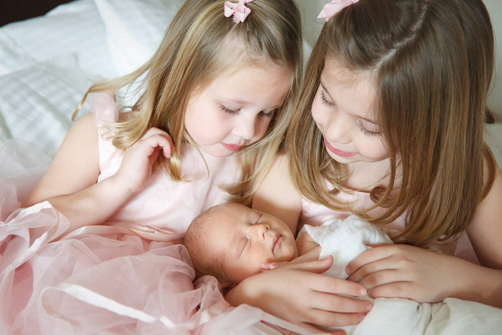 big sisters cuddling new baby brother during photo session