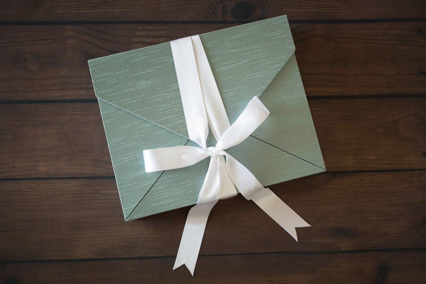 Silk memory portrait box in sage tied with a white silk ribbon