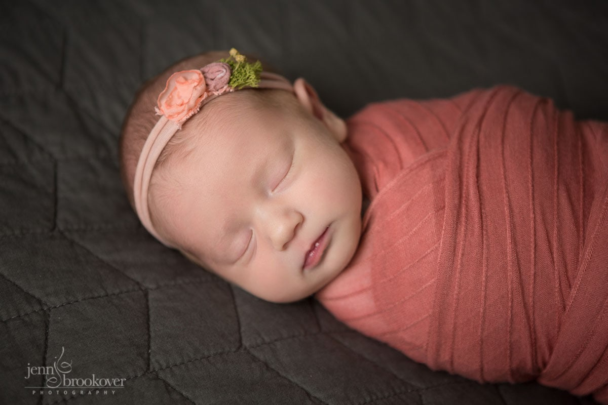sleeping newborn portrait of baby wrapped in coral with flowered headband taken in San Antonio by Jenn Brookover