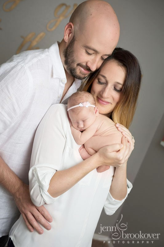 loving family cuddling newborn baby girl during photo session at home in San Antonio taken by Jenn Brookover