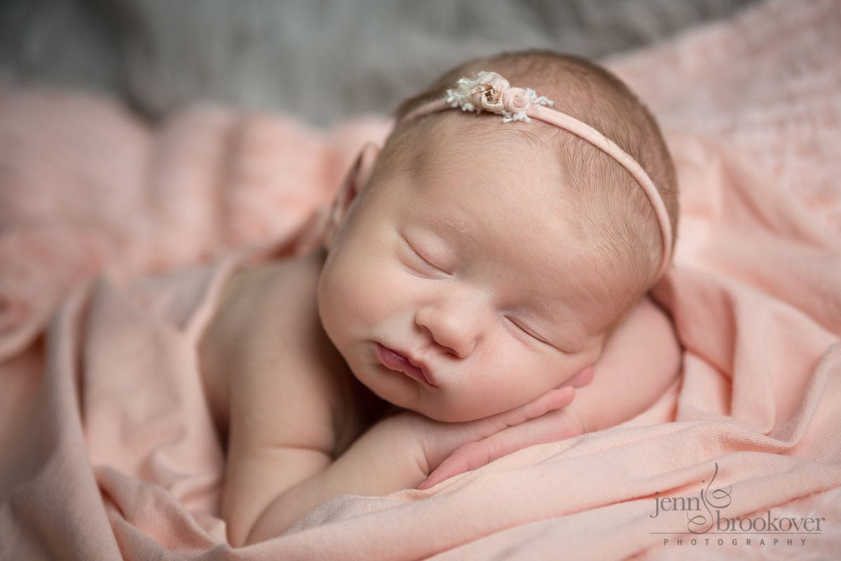 newborn girl wrapped in pink asleep for her newborn portraits in San Antonio
