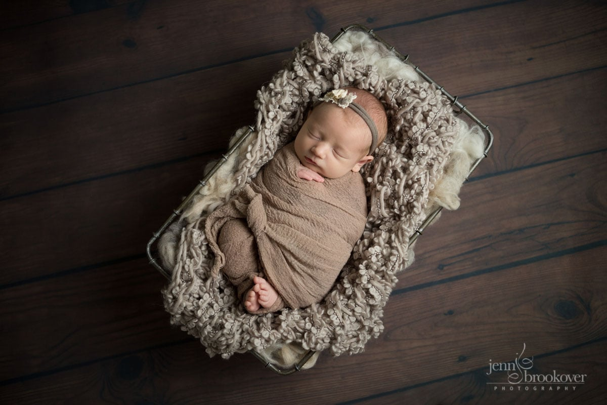baby girl swaddled in taupe resting in a basket asleep during her newborn photo session with Jenn Brookover