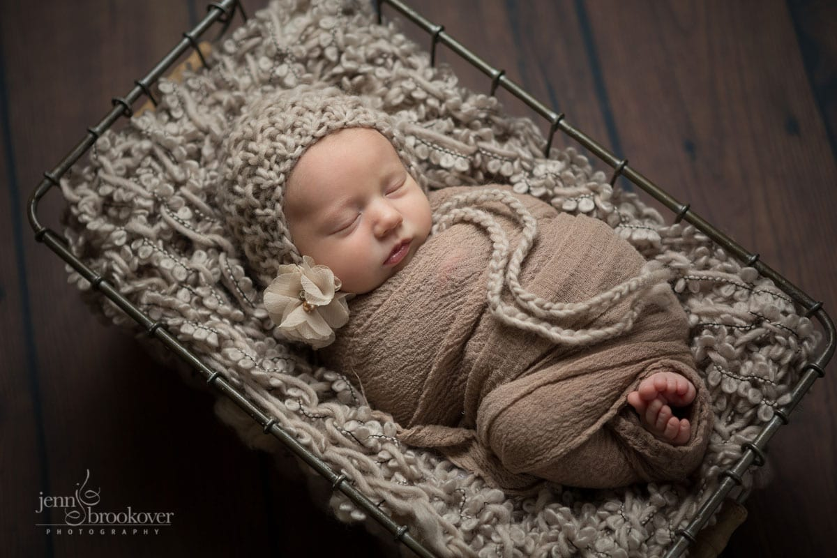 wrapped up two week old newborn girl in taupe wearing a bonnet with flower image by Jenn Brookover