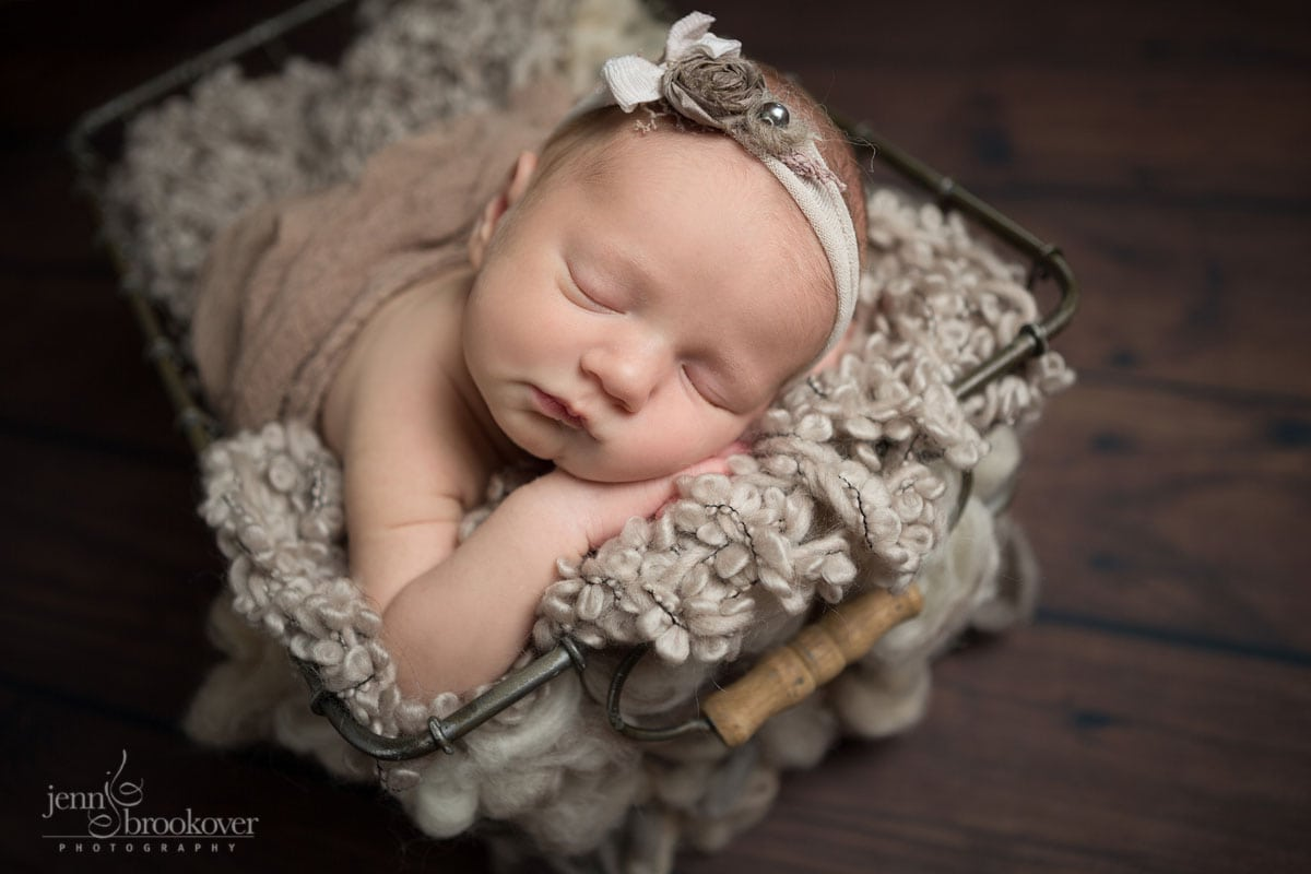 sleeping newborn in a metal basket wrapped in taupe for her newborn photo session with Jenn Brookover