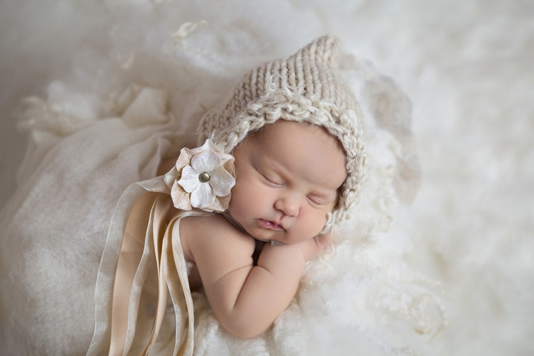 newborn baby girl in a handmade gold bonnet