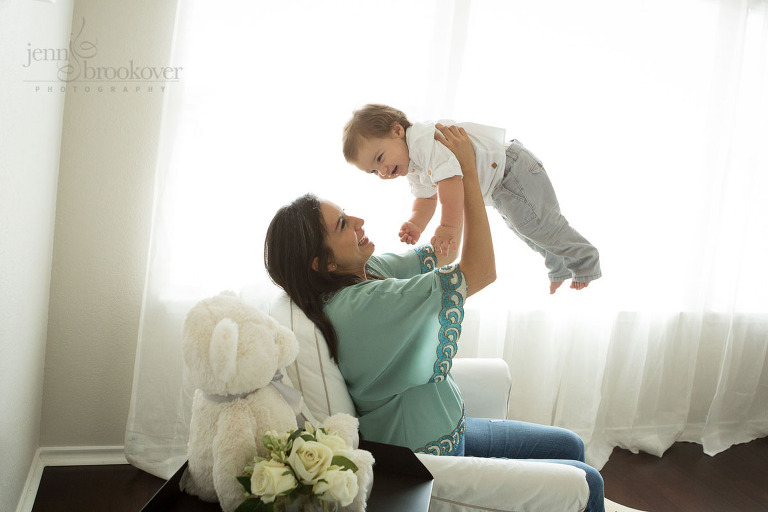 mom holding toddler up in window light