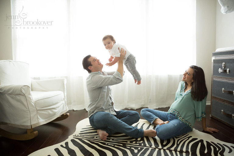 mom dad and toddler at home on a zebra rug during maternity session in San Antonio, Texas