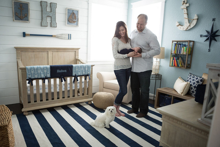 newborn parents and puppy in nautical nursery posted as part of Motherhood Musings feature