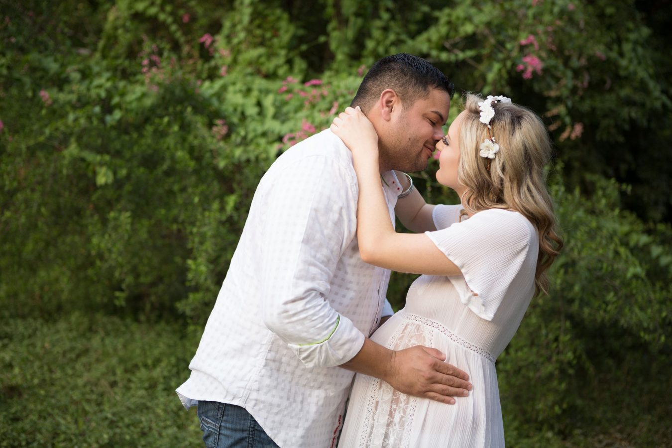couple kissing mom in flower crown during maternity photo shoot in San Antonio at Landa Library
