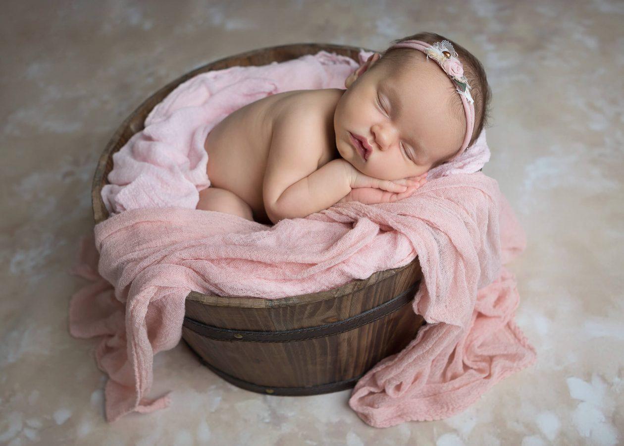 newborn girl in bucket floral pink on a wood floor
