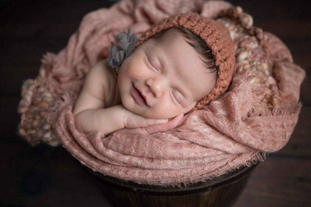 newborn girl smiling in pink San Antonio
