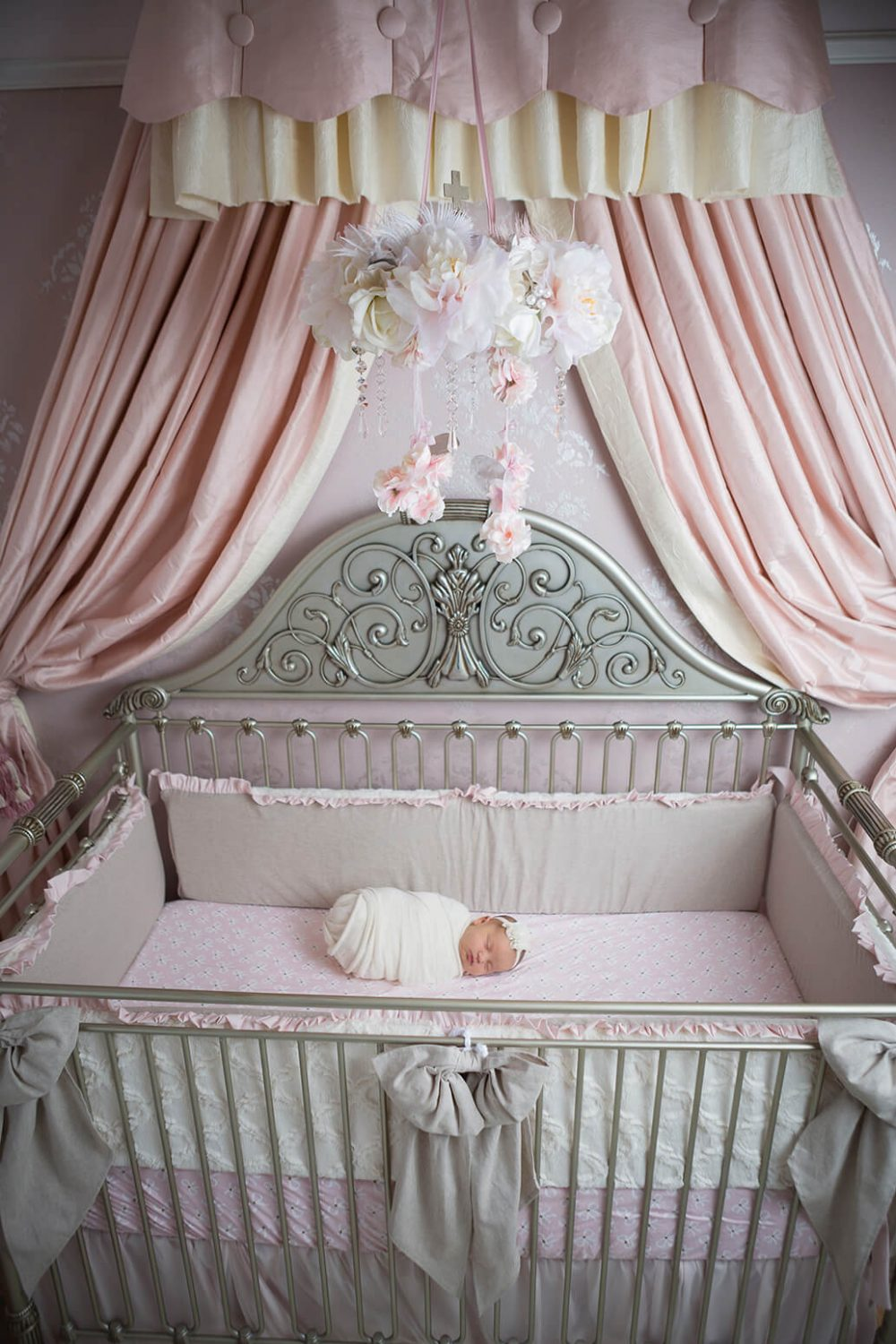 newborn in a custom pink and gray nursery with Caden Lane and Nursery Couture bedding